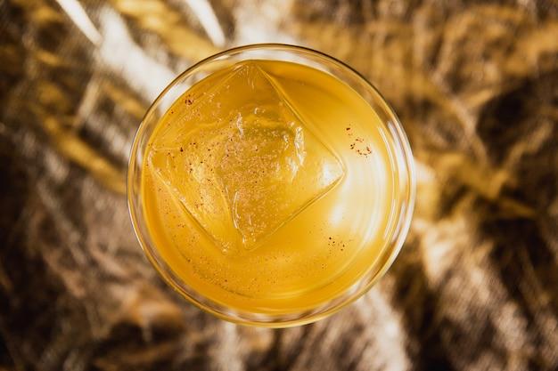 Ярко-желтый коктейль со льдом в бокале rock lowball