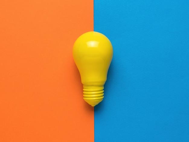 オレンジと青の背景に明るい黄色の電球。ミニマリズム。フラットレイ。