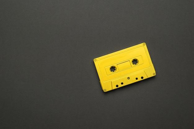 검정색 배경에 밝은 노란색 마그네틱 카세트. 음악을 듣기 위한 세련된 복고풍 장비. 플랫 레이.