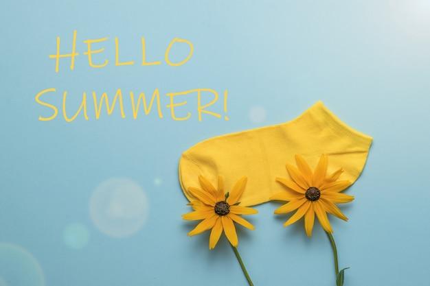 Ярко-желтый носок на двух цветах и надпись hello summer в солнечном свете.