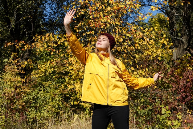 黄色い紅葉と青い空を背景に黄色いレインコートとバーガンディの帽子をかぶった明るい少女。