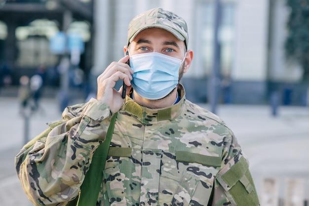 영국 군인이 버스 정류장 밖에 서서 휴대폰을 호출합니다.
