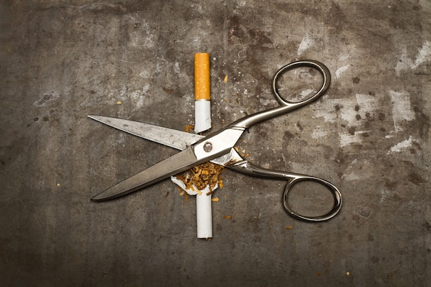 Сломанная сигарета и ножницы на ржавом металлическом фоне