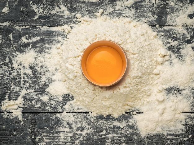 Разбитое яйцо на куче муки на деревянном столе. натуральные продукты и кухонное оборудование.