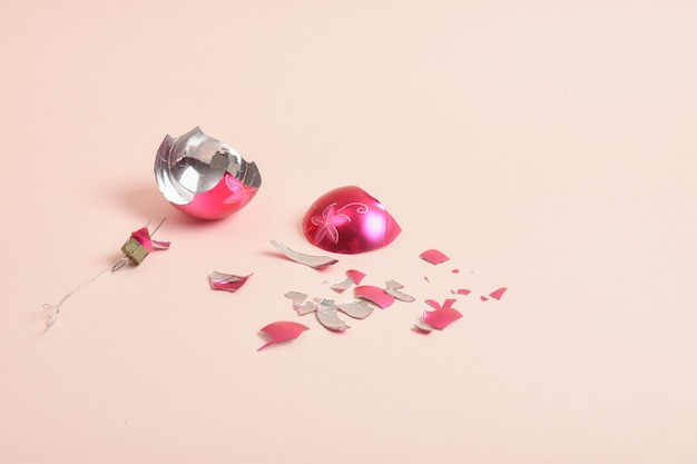 Елочный шар битого стекла на розовом фоне. сломанная елочная игрушка.