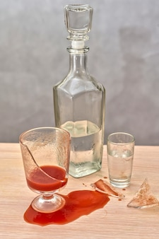 壊れたガラスの赤いトマトジュースがウォッカのボトルの隣のテーブルにこぼれた