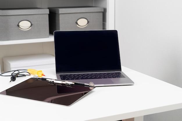 깨진 모니터와 수리된 노트북이 밝은 흰색 방의 테이블에 앉아 있습니다.