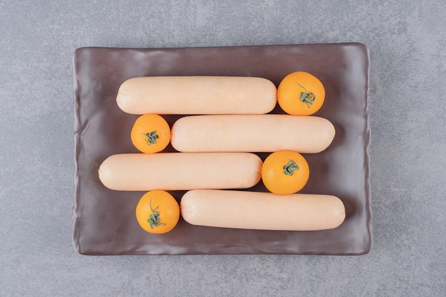 체리 옐로우 토마토와 삶은 소시지의 갈색 보드