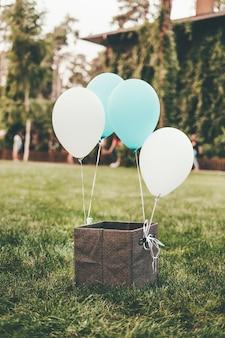 Коричневая коробка стоит на зеленой траве с привязанными белыми и синими воздушными шарами.