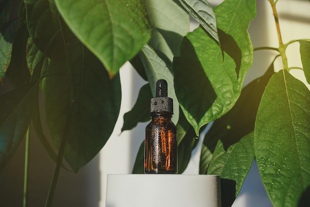 큰 아보카도 잎 가운데 세럼 에센셜 오일 또는 기타 화장품의 갈색 유리 병