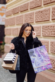 검은 옷을 입은 갈색 머리의 여인이 성공적인 쇼핑을하는 동안 화려한 무늬의 쇼핑백을 들고 있습니다. 밖으로 걸어가는 그녀는 하루의 온기를 즐기고있다