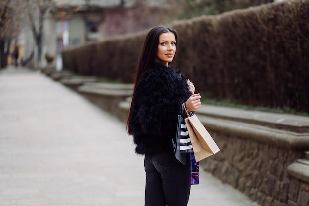 黒の服を着た茶色の髪の女性は、買い物が成功している間、カラフルな模様の買い物袋を持っています。外を歩いて、彼女は一日の暖かさを楽しんでいます