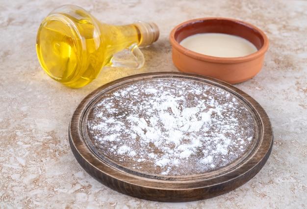小麦粉の茶色のプレートとオイルのガラス瓶