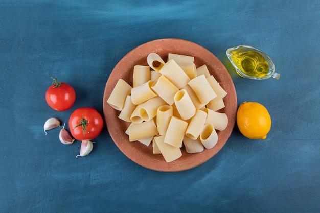 Коричневая тарелка сырых макарон каннеллони со свежими красными помидорами и лимоном на темно-синем фоне.