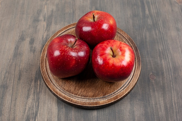 木製のテーブルの上に赤いジューシーなリンゴと茶色のプレート。高品質の写真