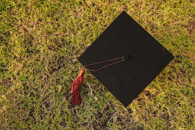 На зеленой траве лежит коричневая черная кепка с кисточками.