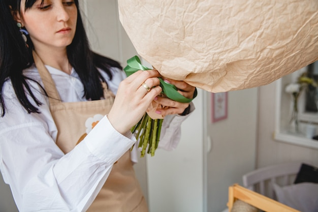 エプロンのブルネットの花屋は、緑のリボンで紙に包まれた花の花束を結びます