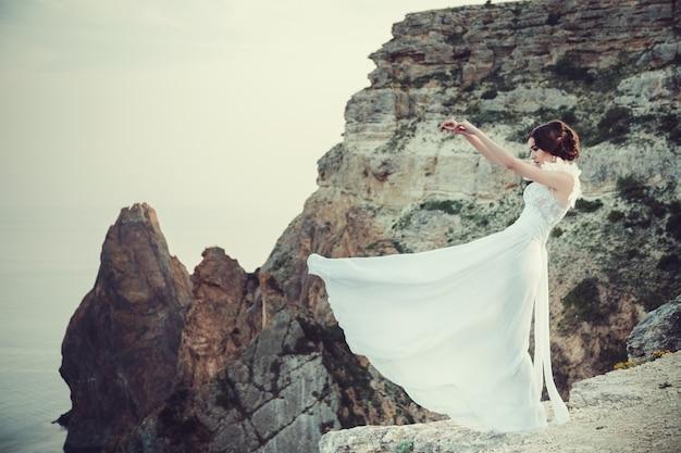 바다 위의 절벽에 천사처럼 아름다운 하얀 드레스를 입고 갈색 머리 소녀, 일몰 춤.