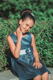 夏に公園に座っている青い水玉模様のドレスを着たブルネットの少女。高品質の写真