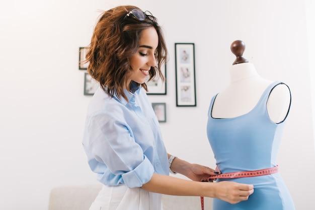 青いシャツを着たブルネットの女の子がワークショップスタジオで働いています。彼女はマネキンの青いドレスを着ています。