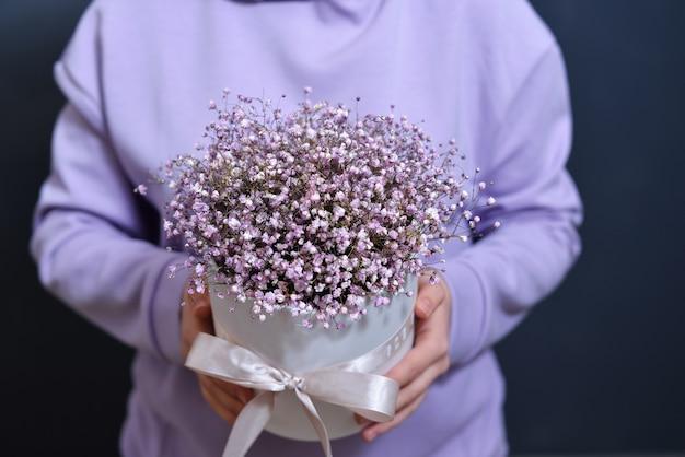 Девушка-брюнетка в нежном фиолетовом свитшоте держит в руках букет.