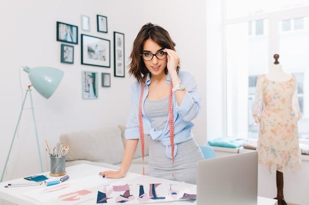 灰色のドレスと青いシャツを着たブルネットの少女は、ワークショップスタジオのテーブルの近くに立っています。彼女はテーブルにたくさんの創造的なものを持っています。彼女はカメラに微笑んでいます。