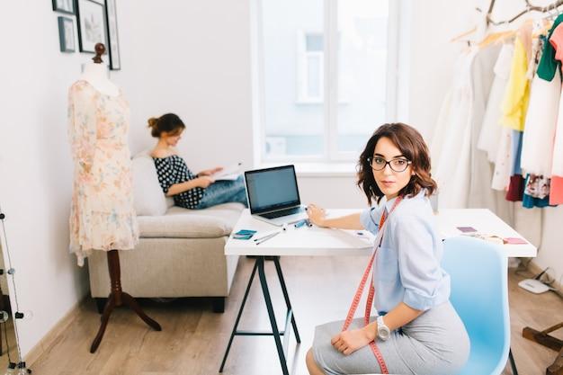 灰色のドレスと青いシャツを着たブルネットの少女は、ワークショップスタジオのテーブルに座っています。彼女はカメラに微笑んでいます。別の一人の女の子が背景のソファーに座っています。