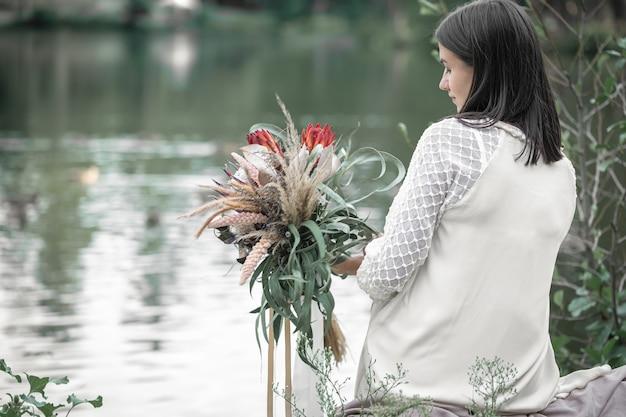 Девушка брюнетка в белом платье сидит у реки с букетом экзотических цветов, размытый фон, вид сзади.