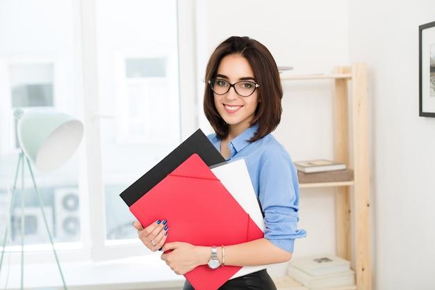 青いシャツを着たブルネットの少女は、オフィスのテーブルの近くに立っています。彼女は手に赤と黒のフォルダーを持っています。