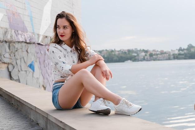 Брюнетка в шортах и кроссовках гуляет по большому озеру. девушка в коротких джинсовых шортах на набережной городского озера.
