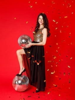 Брюнетка стоит в черном платье с золотыми блестками, держа в руках диско-шар