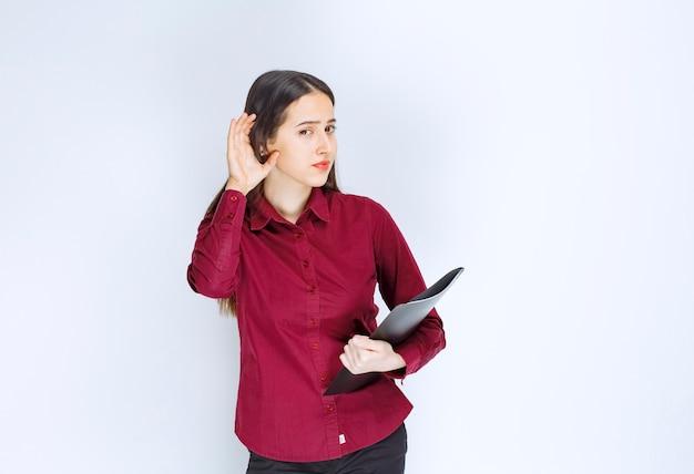 Девушка брюнетка модель стоя и позирует с папкой на белой стене.