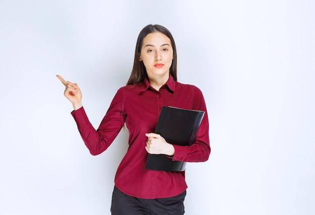 Модель девушки брюнетки стоя с папкой и указывая указательным пальцем.