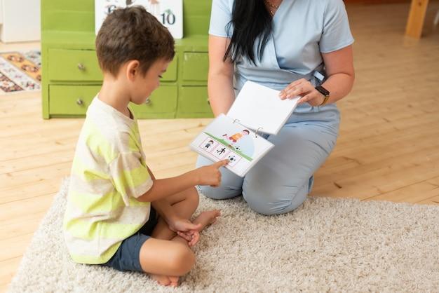 Терапевт брюнетка девушка в синем костюме занимается с ребенком на тренировке с помощью карты