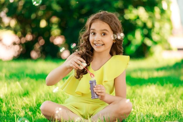 Темноволосая брюнетка сидит на траве в парке и пускает мыльные пузыри. счастливое детство. фото высокого качества