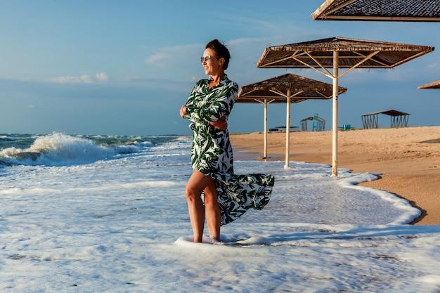 Девушка брюнетка с короткими волосами в платье позирует на пляже возле зонтика от солнца. девушка в платье позирует на пляже