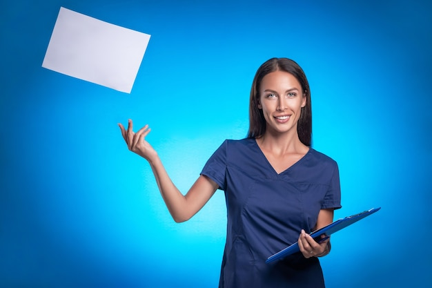 青い手術服を着たブルネットは、片手で録音するための青いタブレットで青い背景に立っている間ポーズをとります。予定のあるシートを空中に投げます。笑顔。医療服。