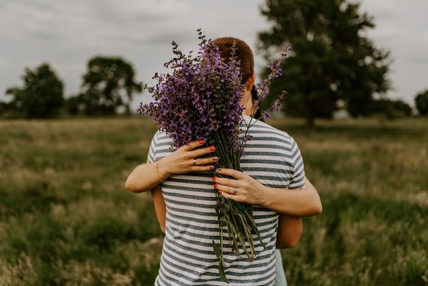 Брюнетка в полосатой футболке стоит в стороне и обнимает женщину.