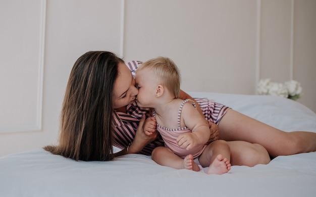 縞模様のパジャマを着たブルネットのお母さんがベッドに横になり、彼女の小さな娘にキスします