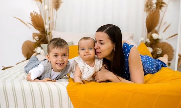 小さな息子と娘を持つブルネットの母親が部屋のベッドに横たわっています
