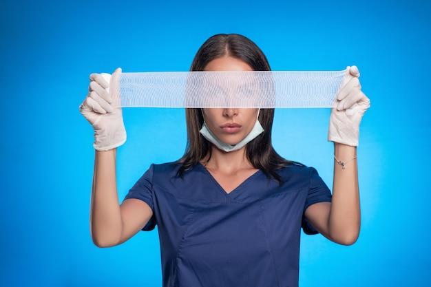 彼女の顔の保護マスク、青い手術服、彼女の手に白い医療用手袋を着用し、彼女の目を覆っている医療包帯で青い背景に立っている間にポーズをとっているブルネット。