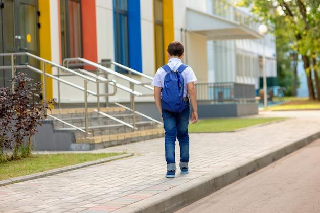 Школьник-брюнетка в белой рубашке, синем галстуке и синем рюкзаке ходит в школу с разноцветными окнами.