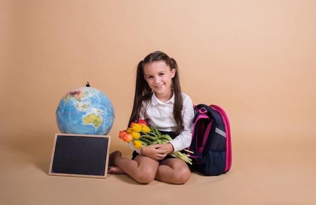 Брюнетка-школьница в форме сидит со школьными принадлежностями и букетом тюльпанов на бежевом фоне с местом для текста