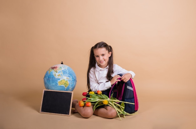 Брюнетка-школьница в форме сидит со школьными принадлежностями на бежевом фоне с местом для текста
