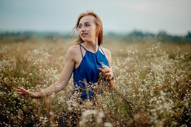 咲くフィールドの真ん中にブルネットの女性の女の子。花粉と花のアレルギー。