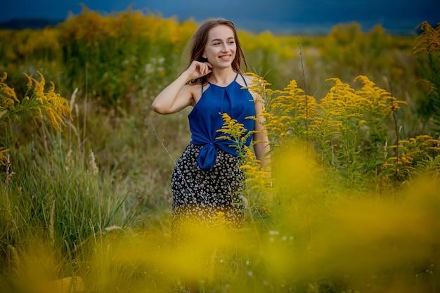 Девушка брюнетка женщина посреди цветущего поля. аллергия на пыльцу и цветение.