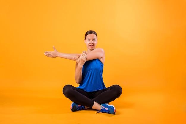 スポーツユニフォームのブルネットの女性はオレンジ色の壁にストレッチします。