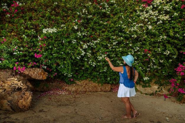 Брюнетка в белой юбке и шляпе от солнца стоит у цветущей белой бугенвиллии.