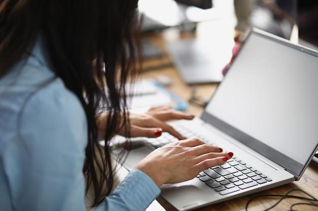 ブルネットの女性がオフィスのテーブルに座って、ラップトップのモダンなコワーキングセンターで働いています