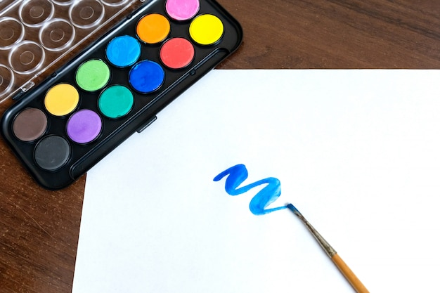 Кисть синей акриловой краски и кисть рядом с ней. изолировать на белом фоне